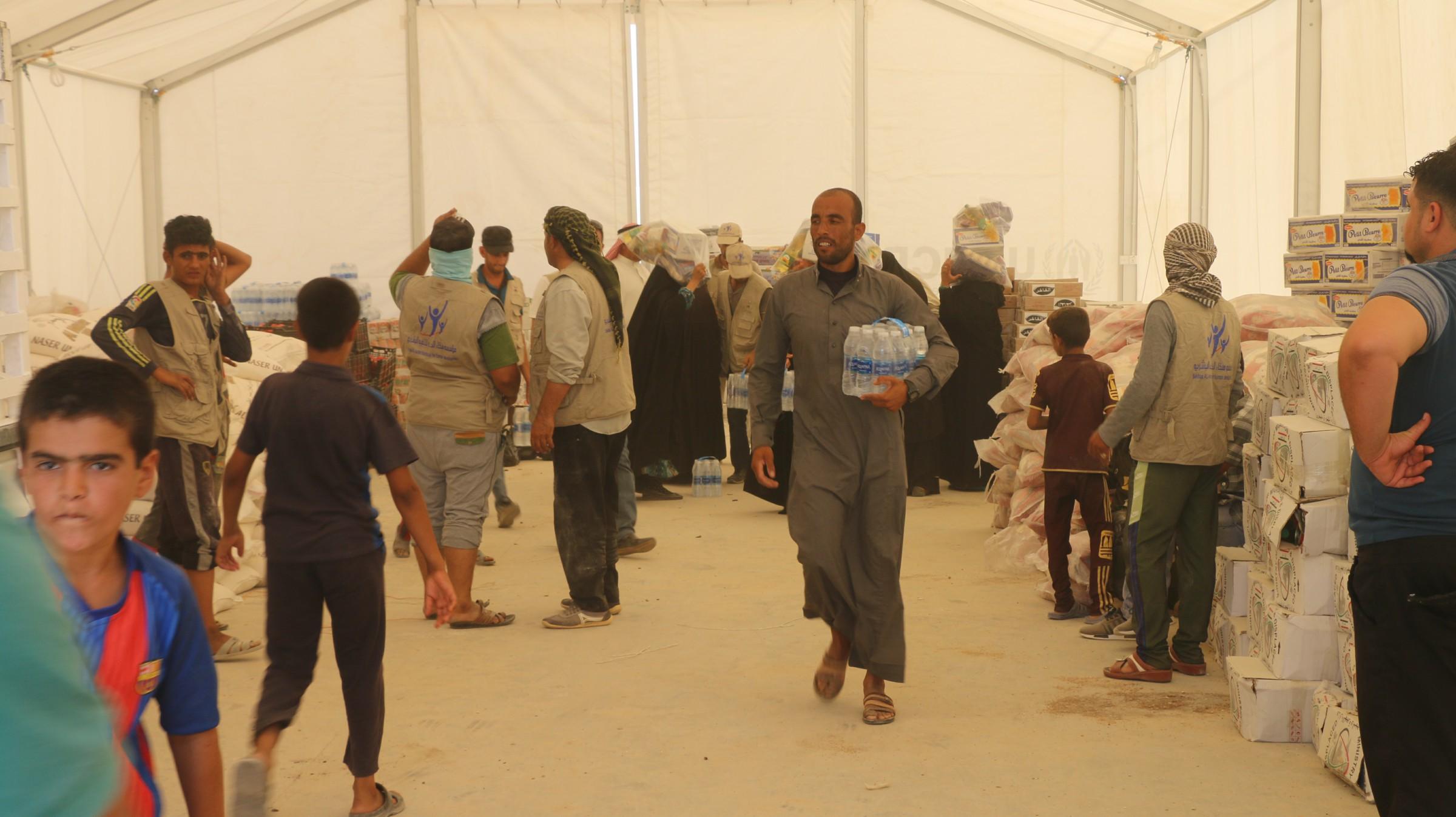 توزيع 1500 حصة غذائية بين نازحي مخيم 18 كيلو في الرمادي
